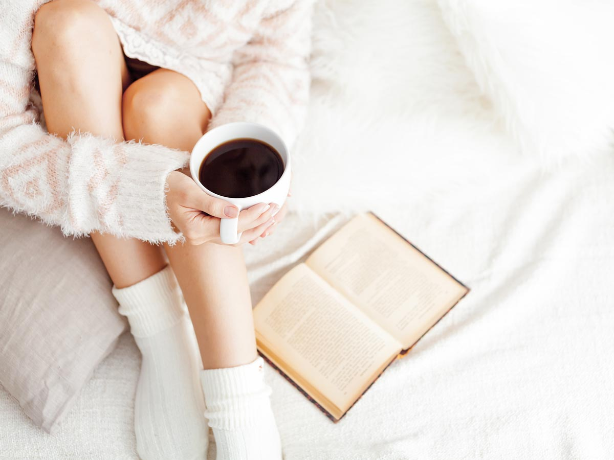Woman on white bed holding coffee cup reading book about benefits of simplifying your life