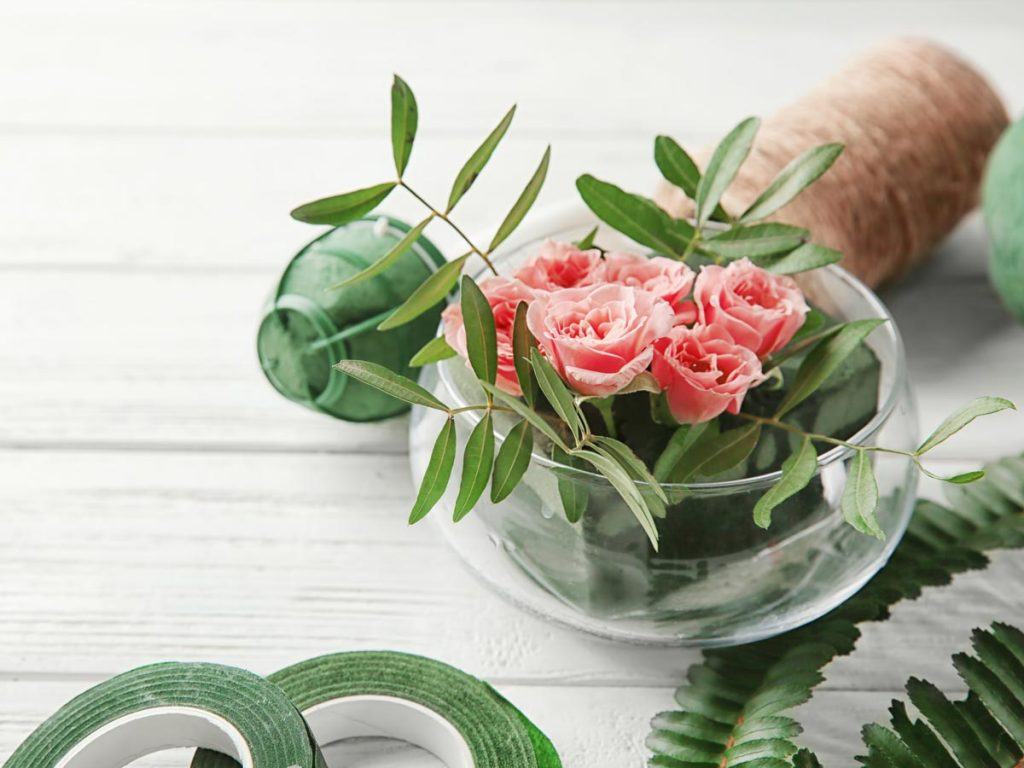 Pink roses with green leaves in glass bowl on white table