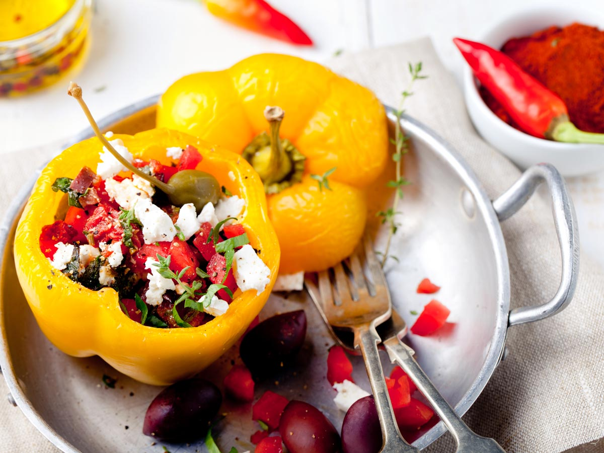 Yellow stuffed bell pepper with feta and tomato on metal tray