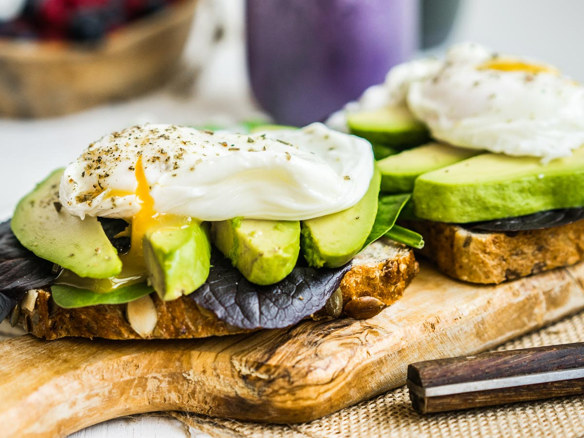 Avocado and fried egg sandwich on wooden board