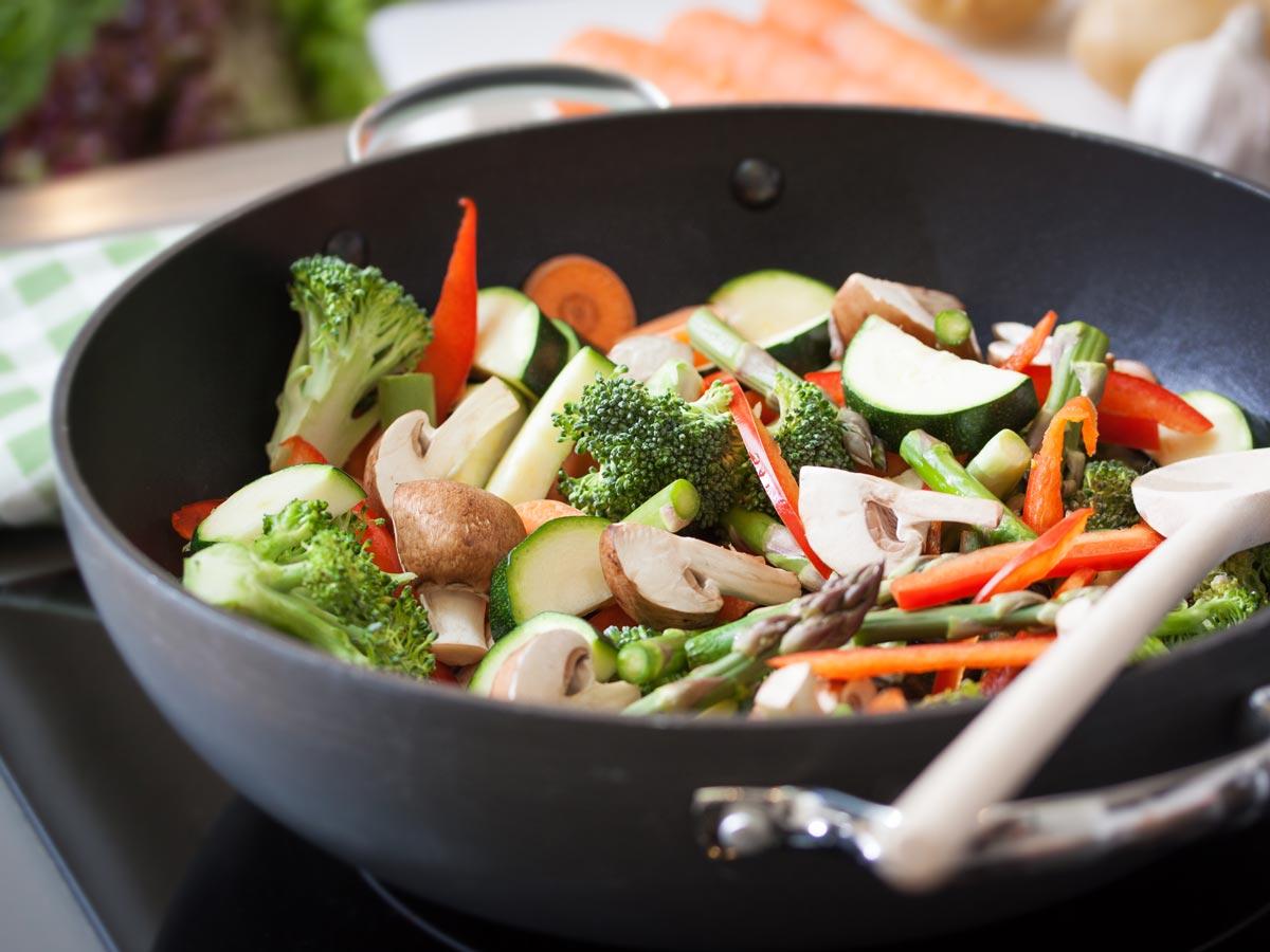 Broccoli, zucchini, pepper stir fry in black wok