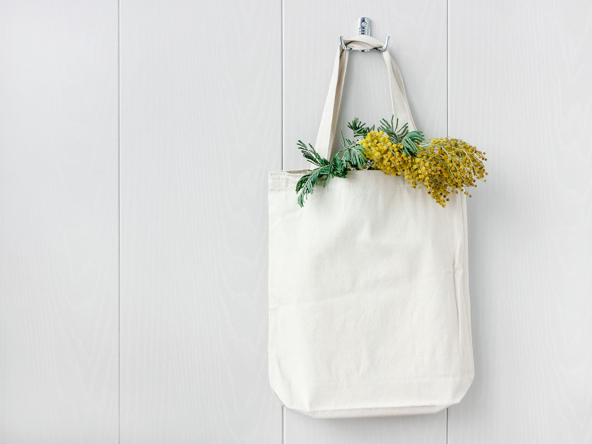 White eco friendly bag with yellow flowers hanging on white wall