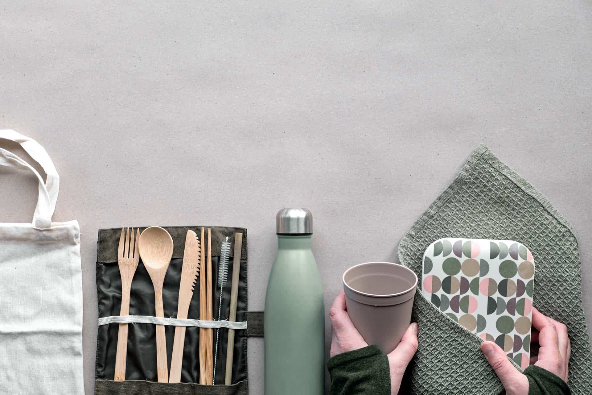 Flatlay of low impact living products - white tote bag, wood cutlery, reusable bottle