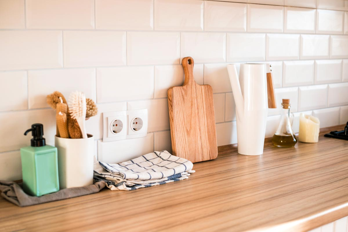 Wood kitchen counter with soap, brushes, towel, and white tile backsplash