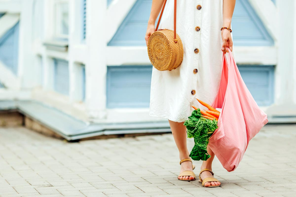 Woman in white dress holding pink produce bag with carrots insdie