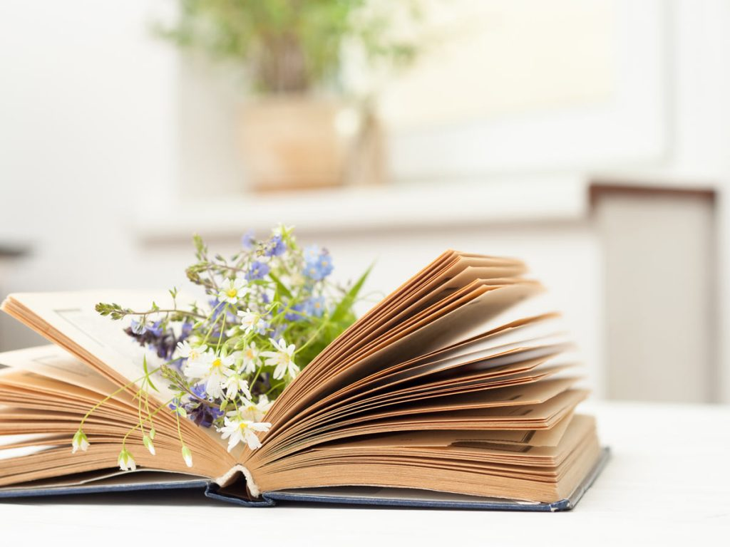 Open book of simple living quotes with wildflowers inside on white table
