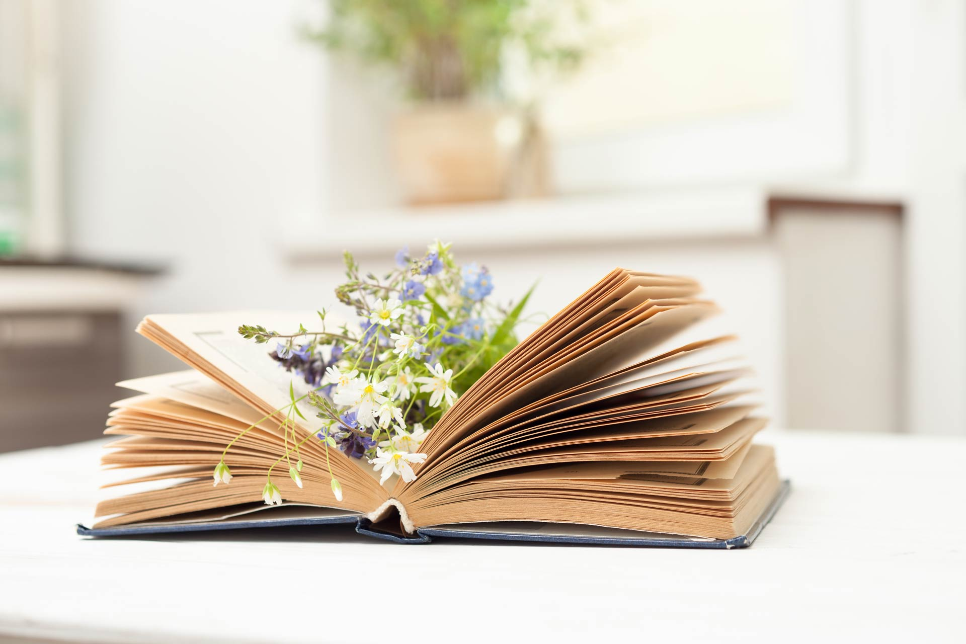 Book of simple living quotes with flowers inside on white table