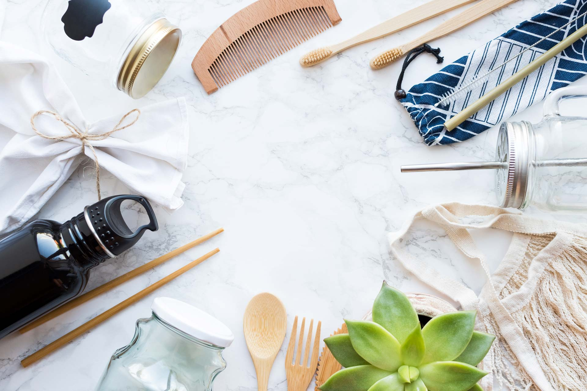Sustainable living ideas flatlay with wooden utensils, succulent, and glass bottles