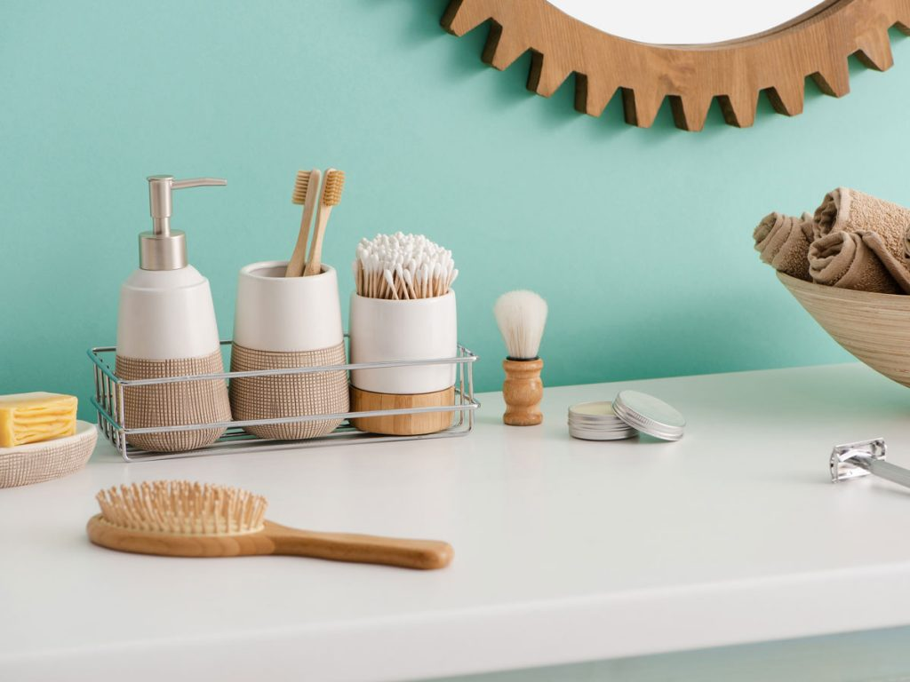 Bathroom counter with sustainable bamboo products including hairbrush, toothbrushes, and makeup brush