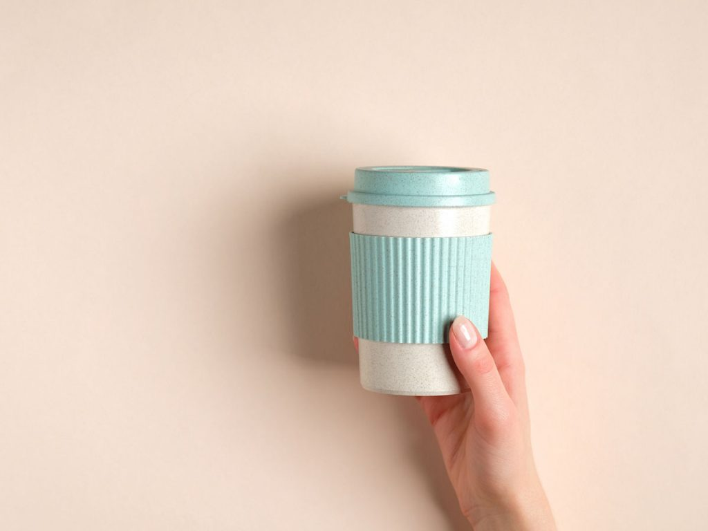 Hand holding blue and white reusable bamboo cup against peach background
