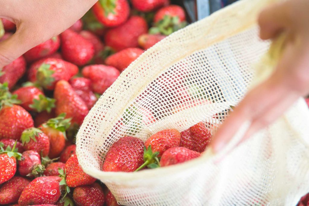 Person putting strawberries from bin into mesh bag, using low-waste living tips at market