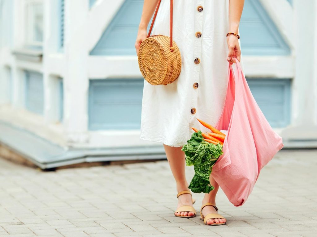 Girl in white dress carrying pink bag of produce using low-waste living tips