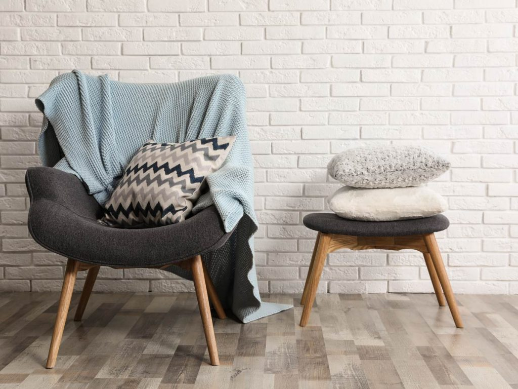 Grey chair and stool with throw pillows and blankets piled on top, in front of white brick wall