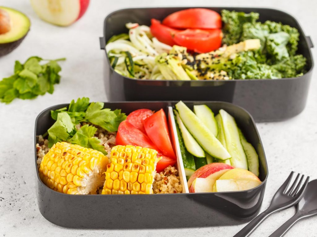 Two black meal prep containers with salads, sitting on white countertop