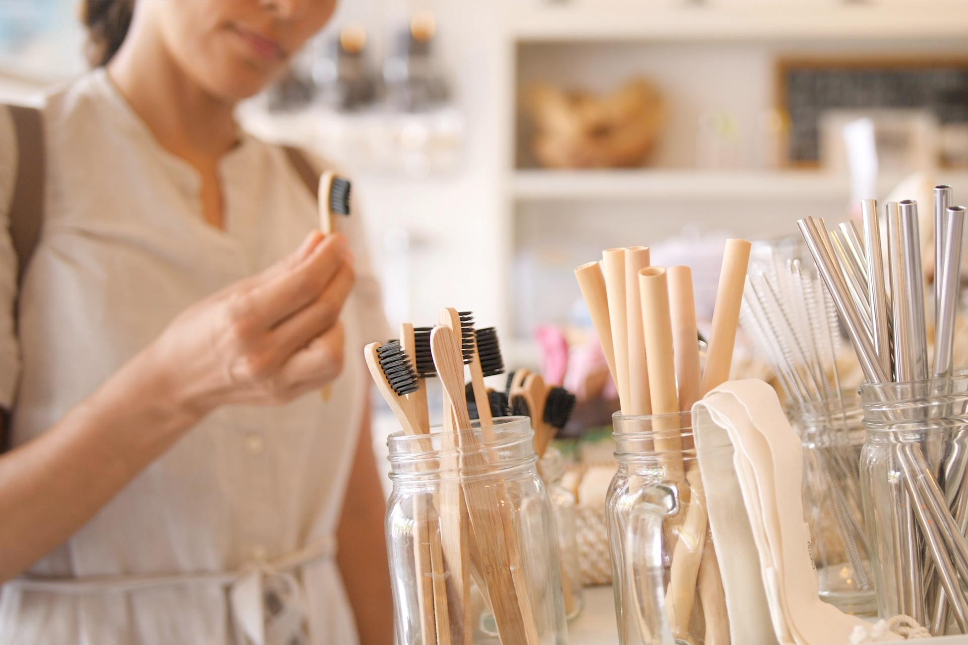 Woman shopping for sustainable living products including toothbrushes and straws