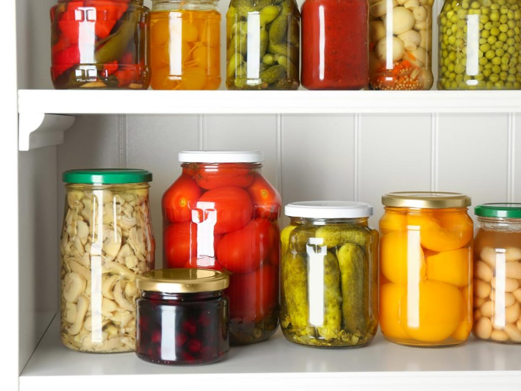 Six glass jars each containing preserved fruit and vegetables, sitting on white shelf