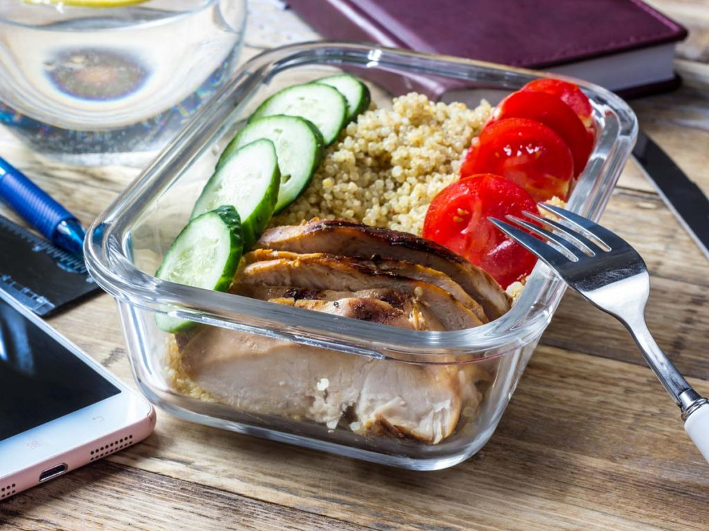 Chicken, cucumber, tomato, and couscous in glass container sitting on wood desk, with silverware and phone