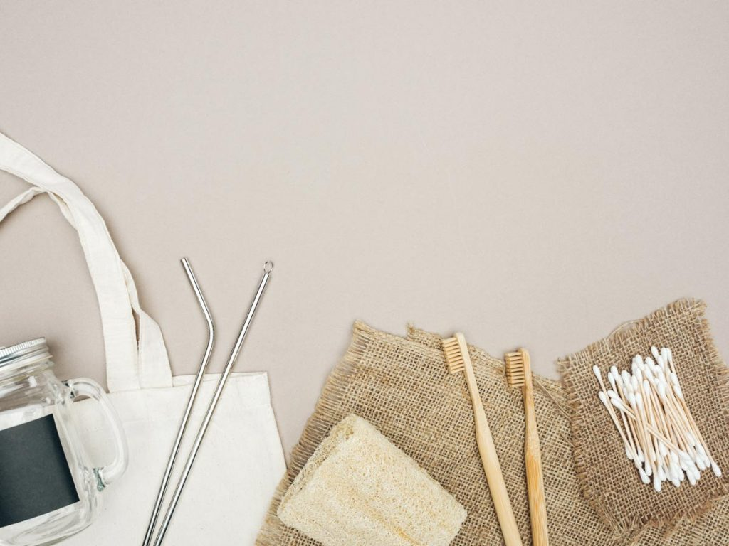 Flat lay of easy plastic swaps - bamboo toothbrush, cotton swabs, metal straw, glass jar, and canvas bag