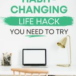 """White desk with laptop and lamp, with text overlay - """"the habit changing life hack you need to try""""."""