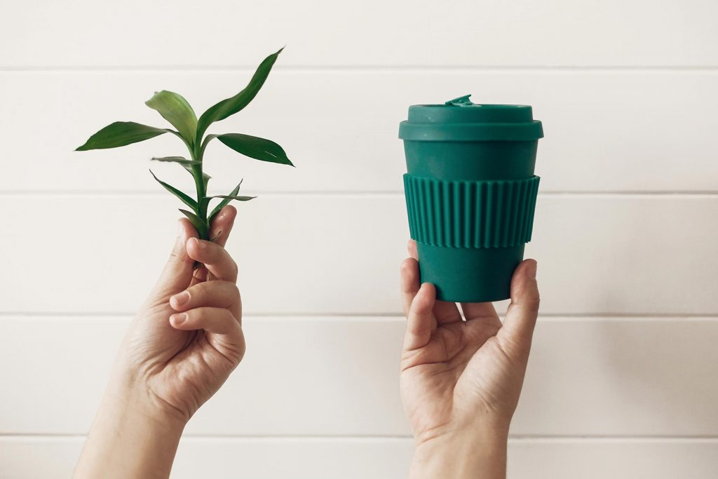 Hands holding up green plant stem and reusable coffee mug, depicting zero waste vs low impact dilemma