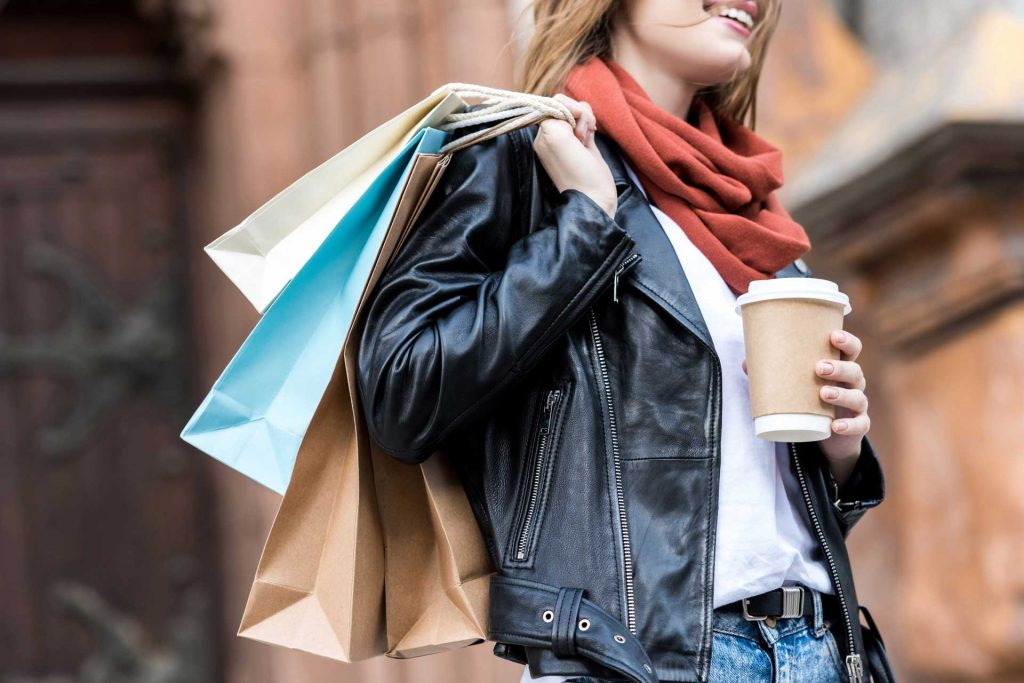 Woman holding coffee and shopping bags, illustrating fast fashion vs slow fashion