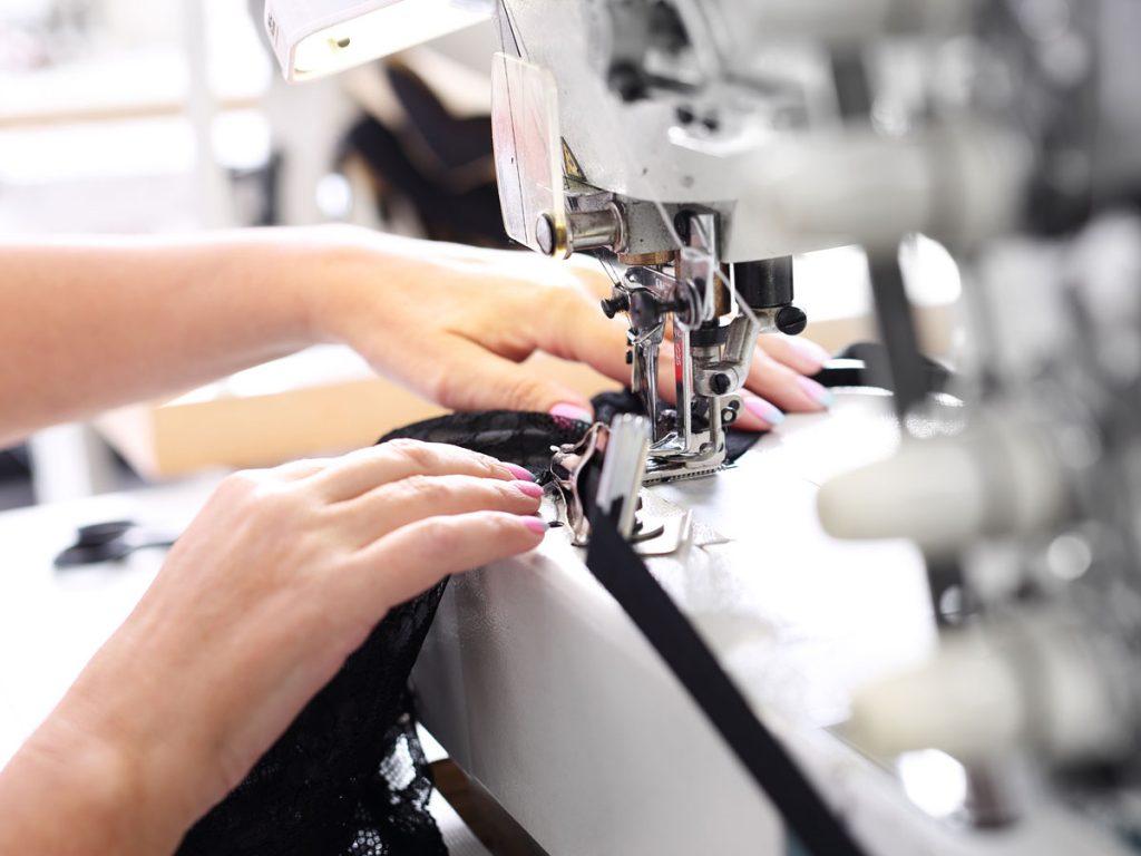 Hands working black fabric through sewing machine