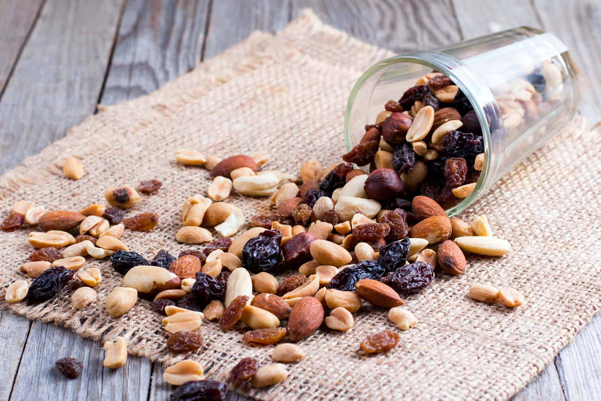 Popular zero waste snacks of nuts and dried fruit spilling from jar onto napkin