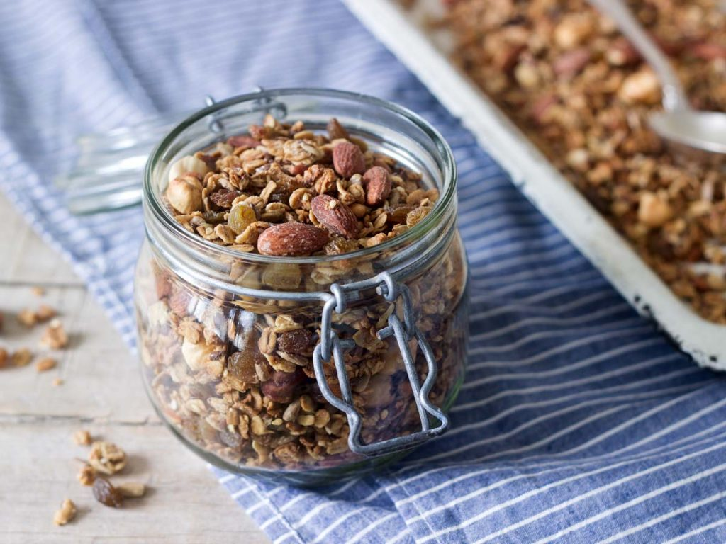 Glass jar of granola on top of blue and white striped towel