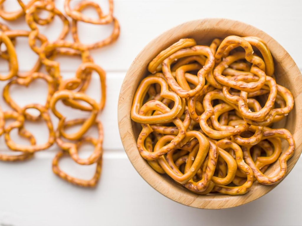Wooden bowl of heart-shaped pretzels with more pretzels on table