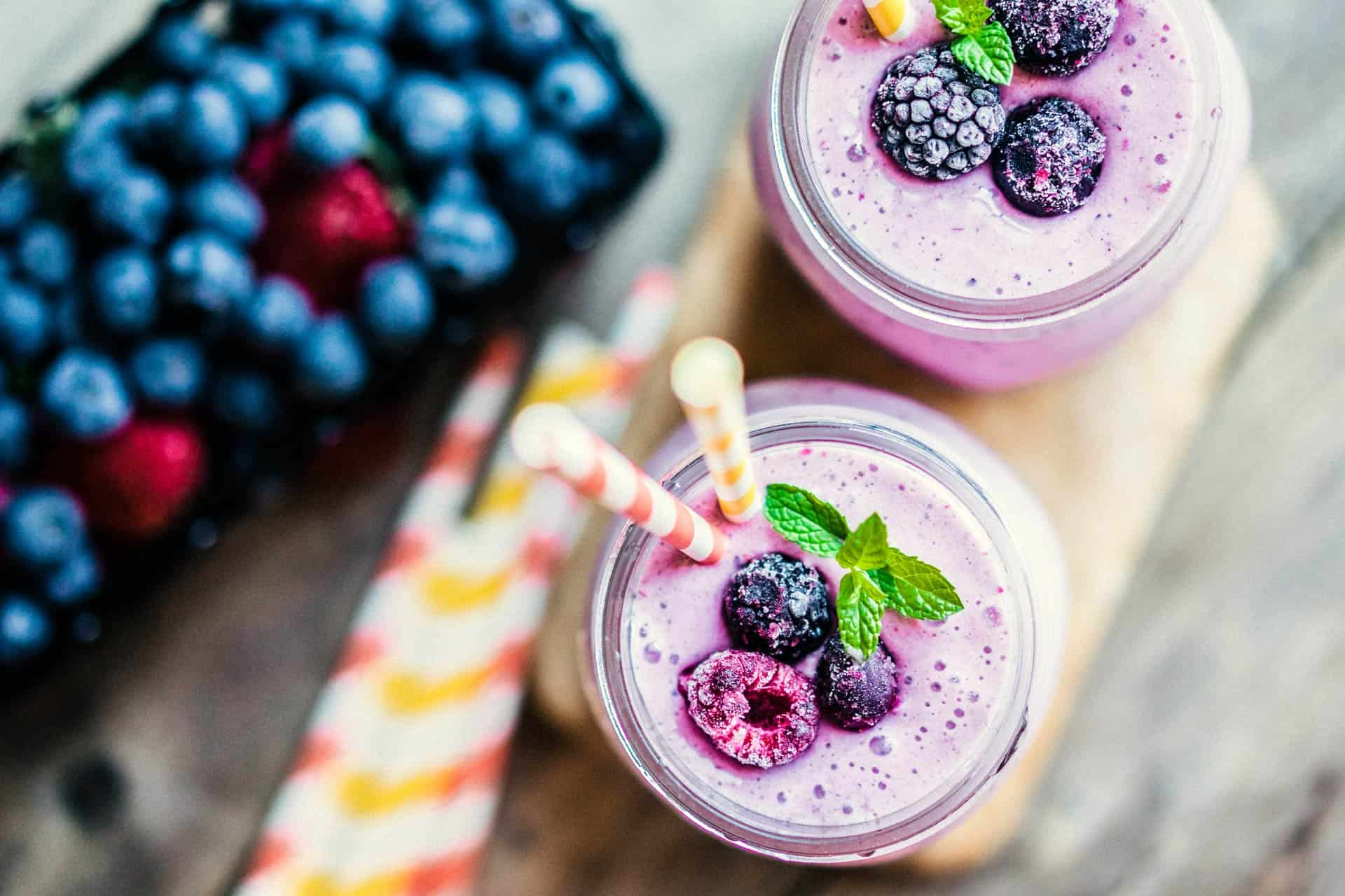 Two blueberry smoothies in frozen mason jars with tray of berries