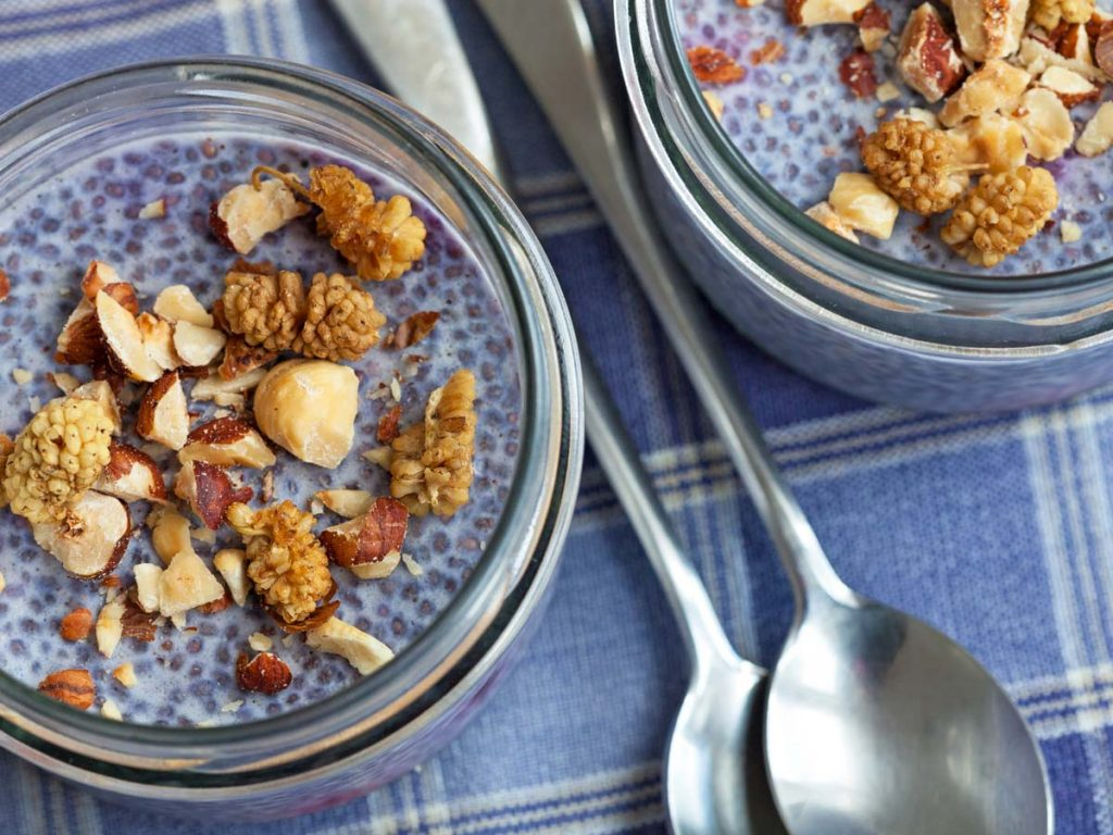 Two portions of chia pudding topped with granola being prepared for freezing mason jars