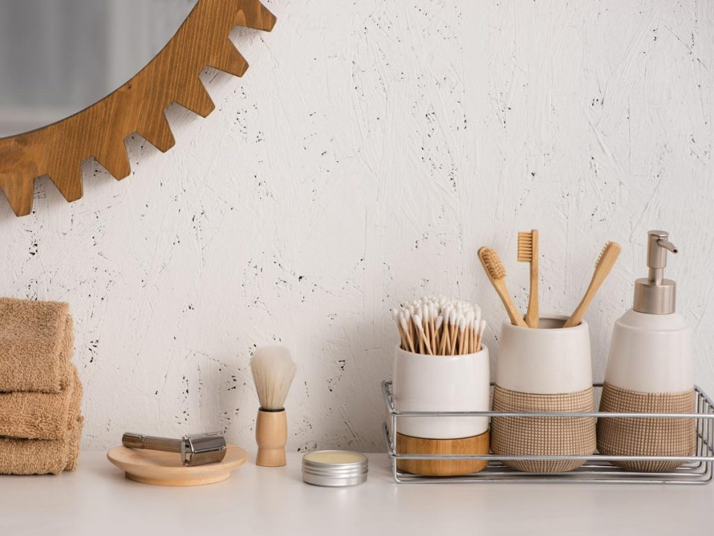 Bathroom counter with zero waste swaps inside jars, including bamboo toothbrushes, cotton swabs, and soap