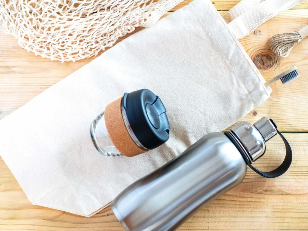 Flat lay of canvas bag, reusable coffee cup and steel water bottle on top of wooden table