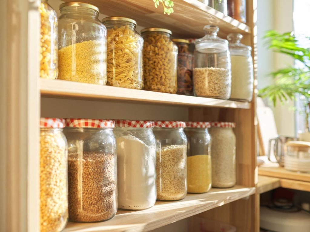 Wooden shelves of glass jars containing seeds, grains, and pastas, popular zero waste swaps