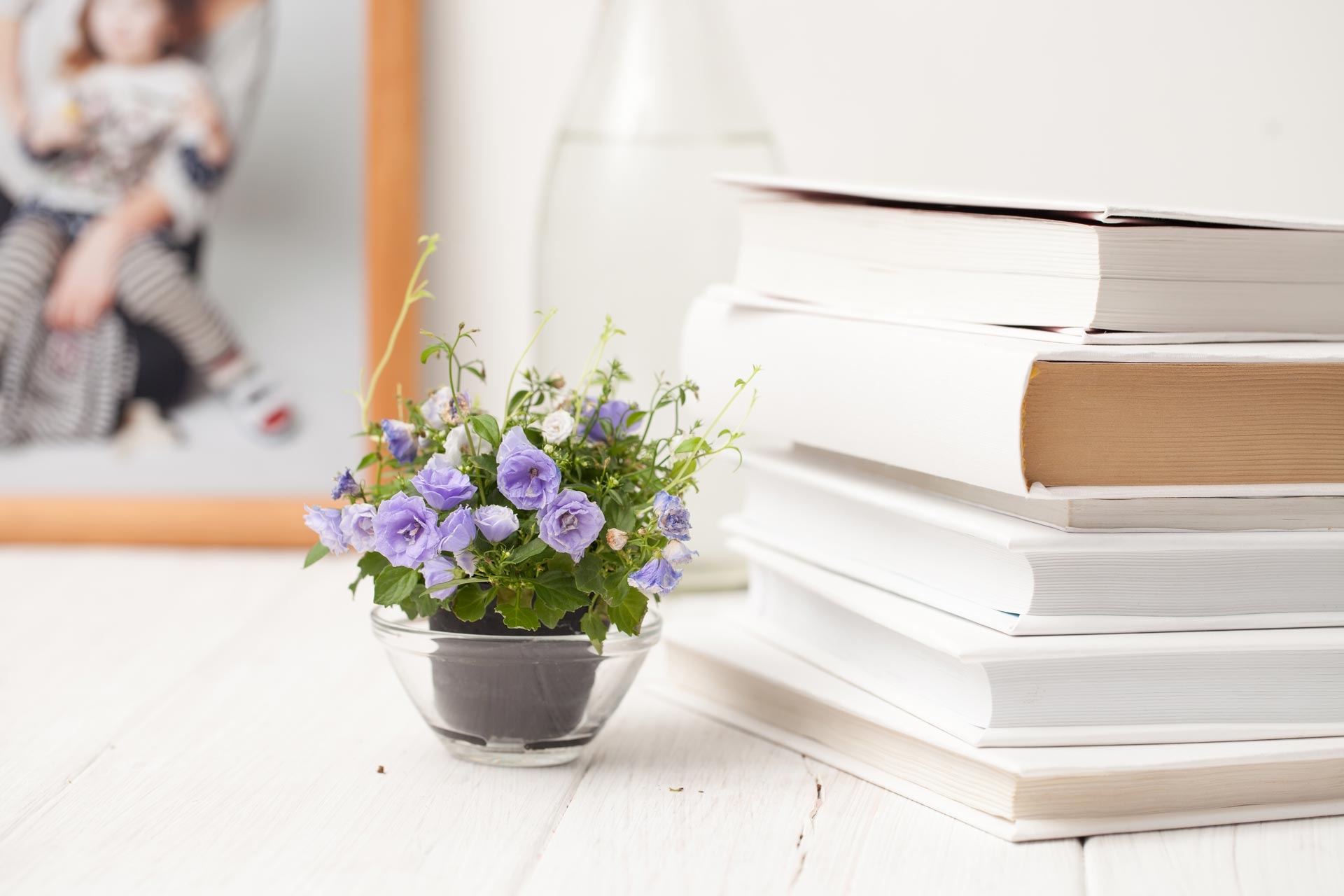 Stack of best books on simple living next to purple flowers on white table