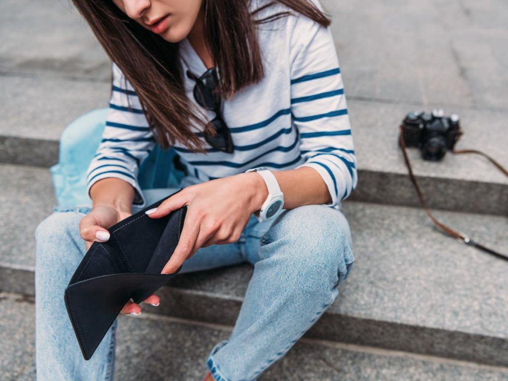 Young woman sitting on concrete steps holding empty eco friendly wallet.
