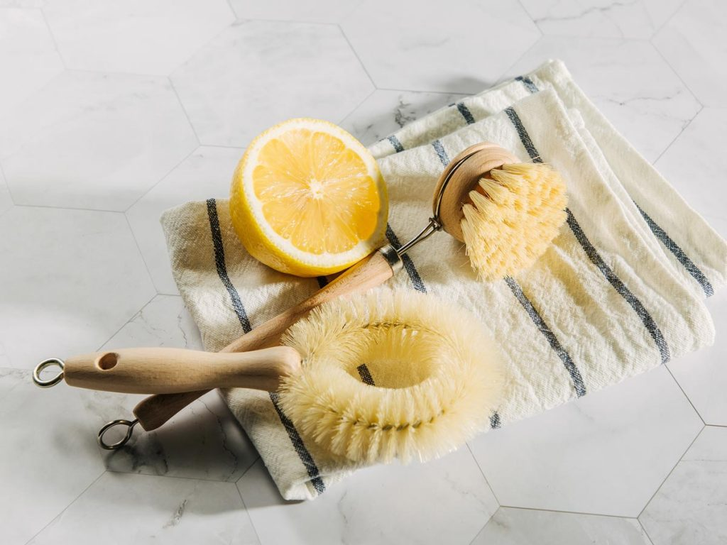 Two bamboo dish brushes and half of a lemon sitting on blue and white striped towel.