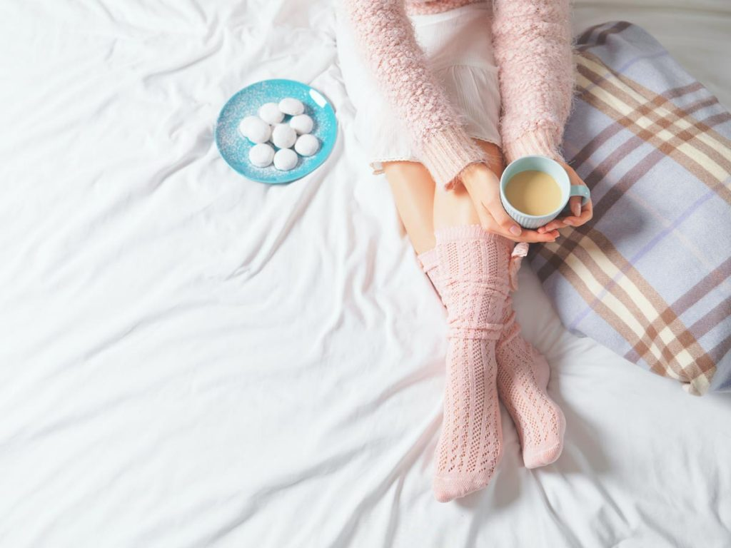 Girl in pink pajamas sitting on white bed holding coffee, living a simple life.