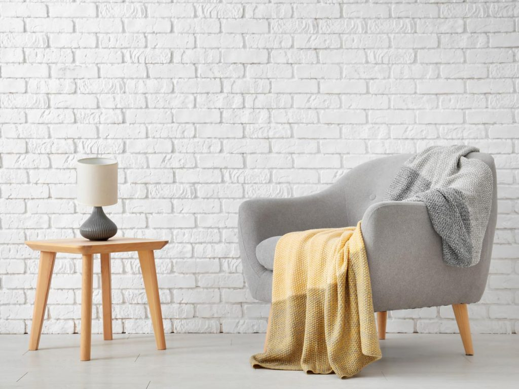 Minimalist living room with grey chair, yellow blanket, and wooden table in front of white brick wall.