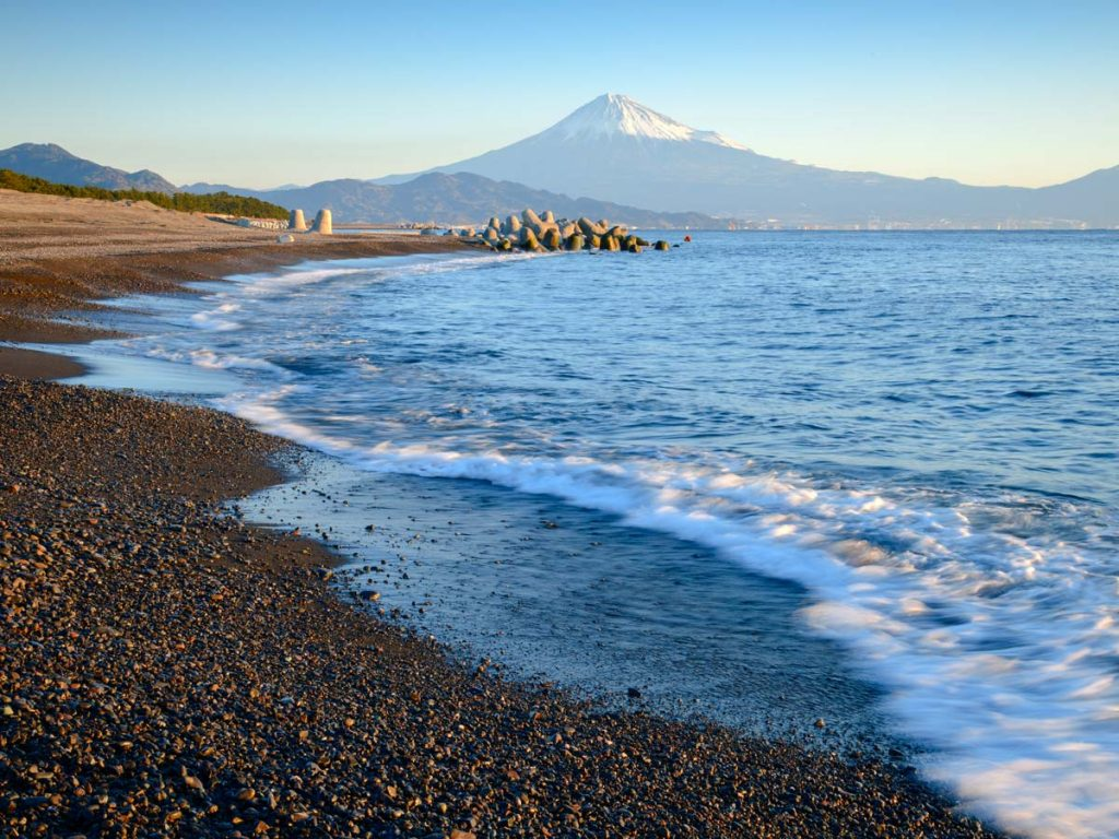 Ocean beach at sunset with view of Mount Fuji in the distance.