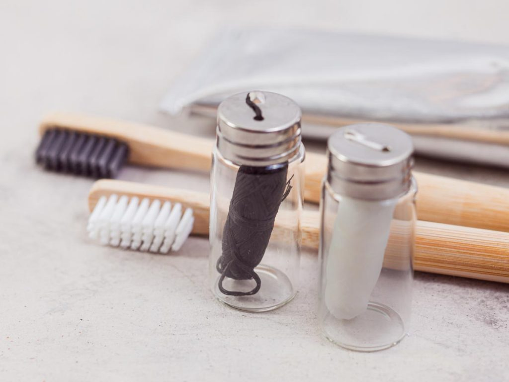 Two glass jars of zero waste floss in front of two bamboo toothbrushes