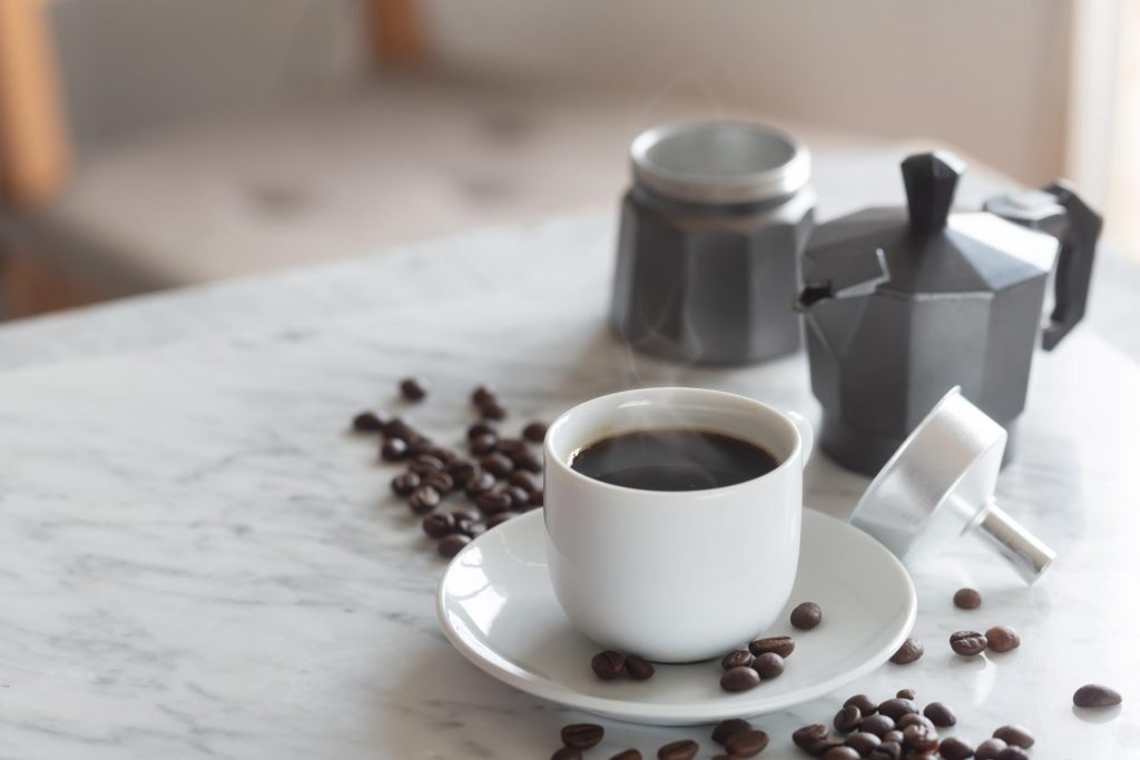 White coffee cup and saucer with freshly brewed zero waste coffee, sitting next to metal espresso maker on countertop.