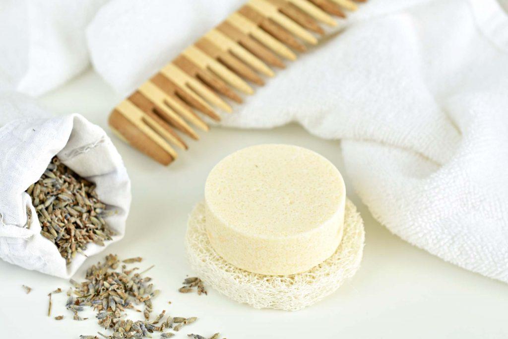 Cream-colored zero waste shampoo bar next to white towel, lavender grain, and wooden comb.