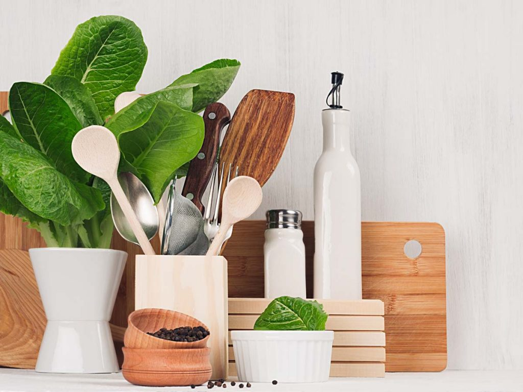 Closeup view of various containers holding eco friendly kitchen products and leafy greens.