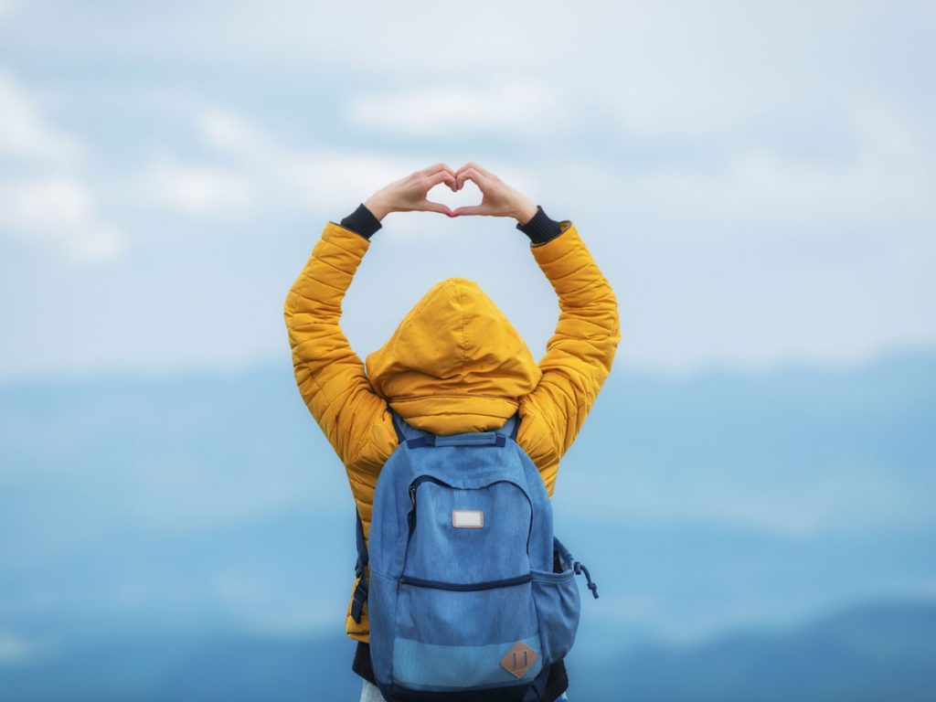 Woman wearing yellow jacket and blue eco friendly backpack.