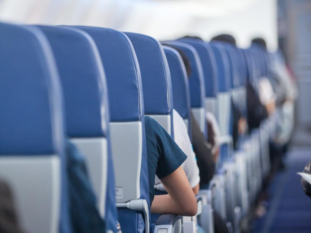 Interior of airplane with aisle full of blue chairs.