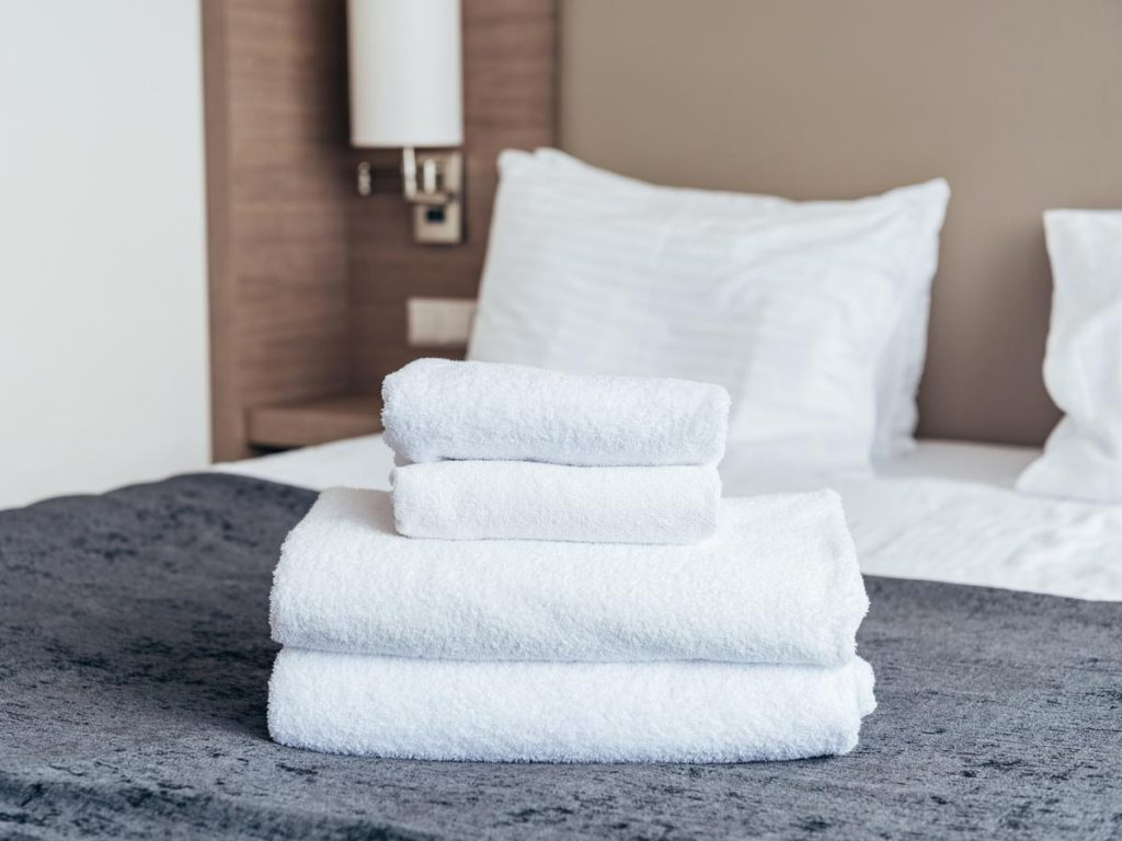 Hotel bed with grey cover and pile of white, folded towels on top.