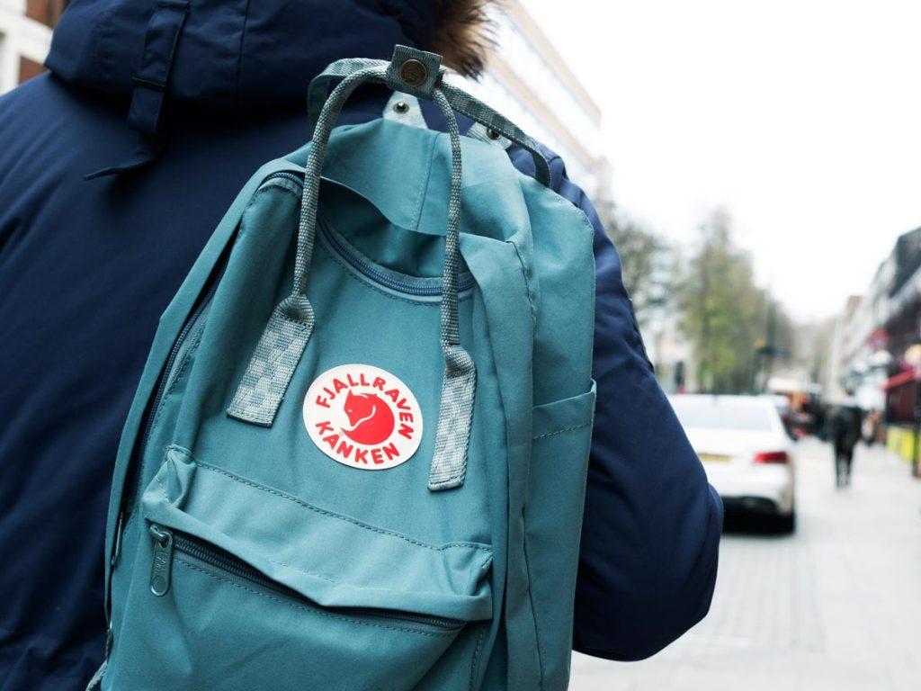 Man wearing blue eco friendly travel backpack walking down street.