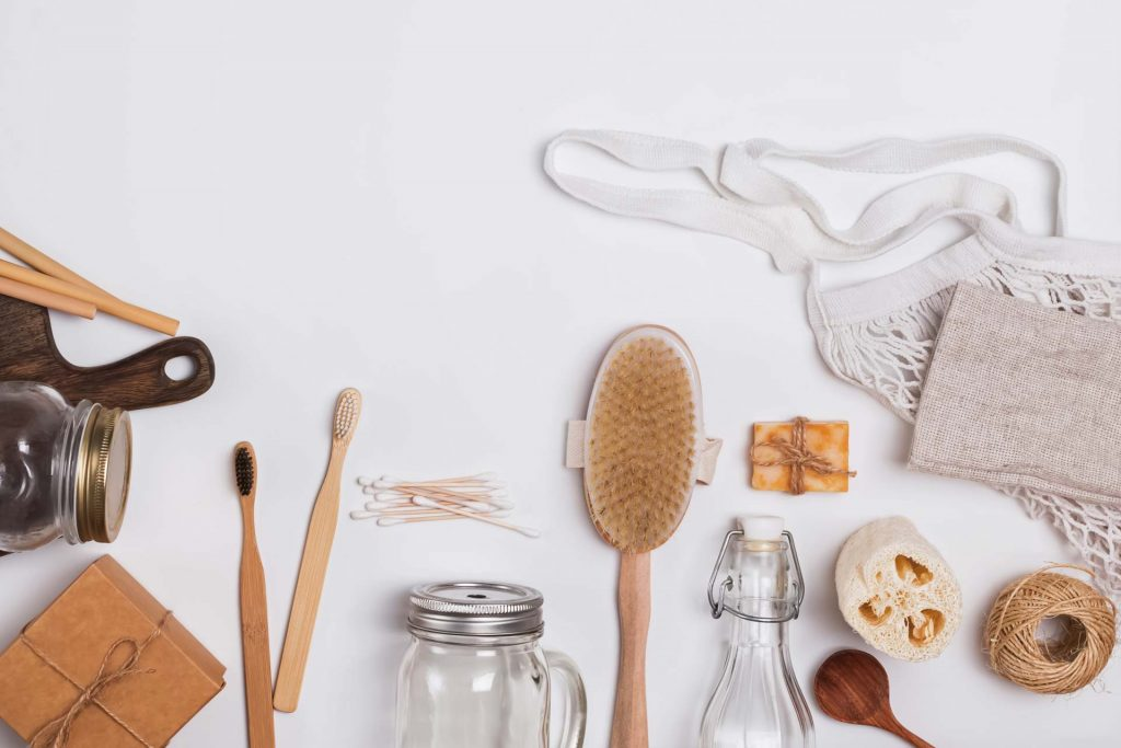 Flat lay of products for zero waste living, including wooden hair brush, bamboo toothbrushes, linen bag, and mason jar.