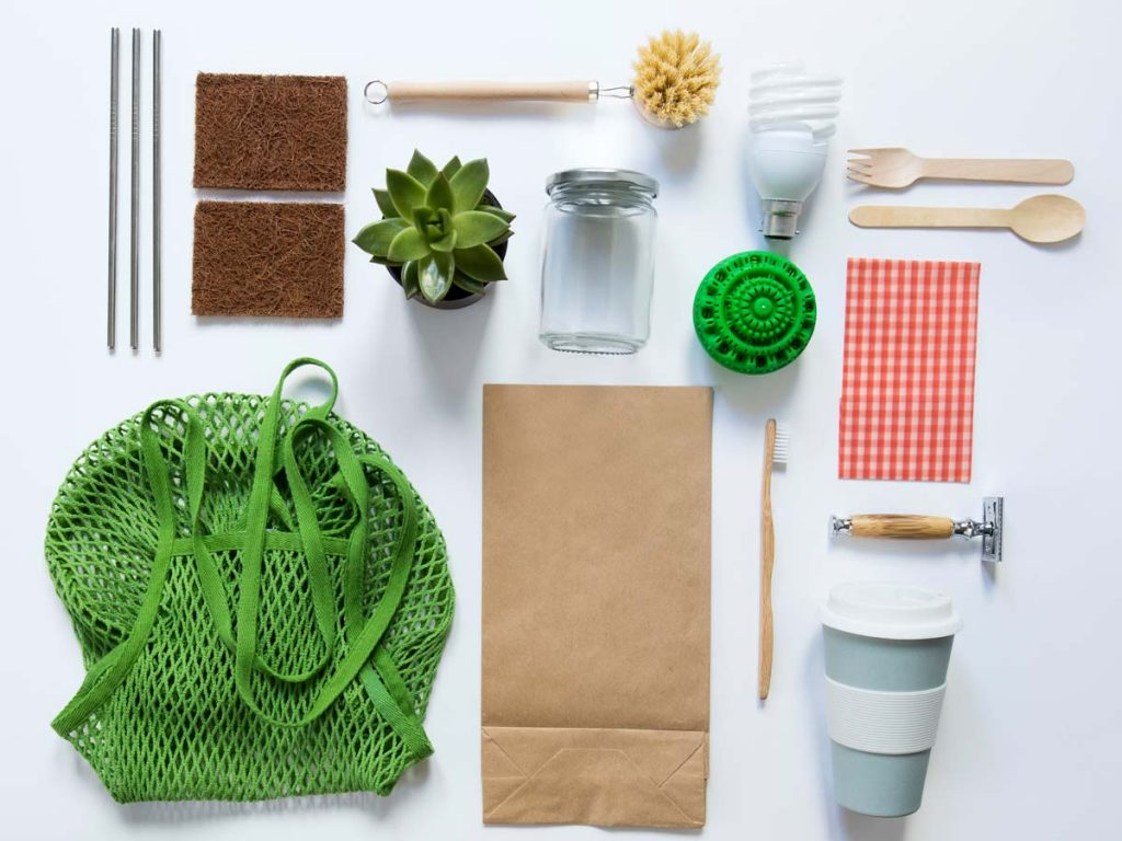 Flat lay of zero waste living products, including razor, bags, coffee mug, toothbrush, and sponges.